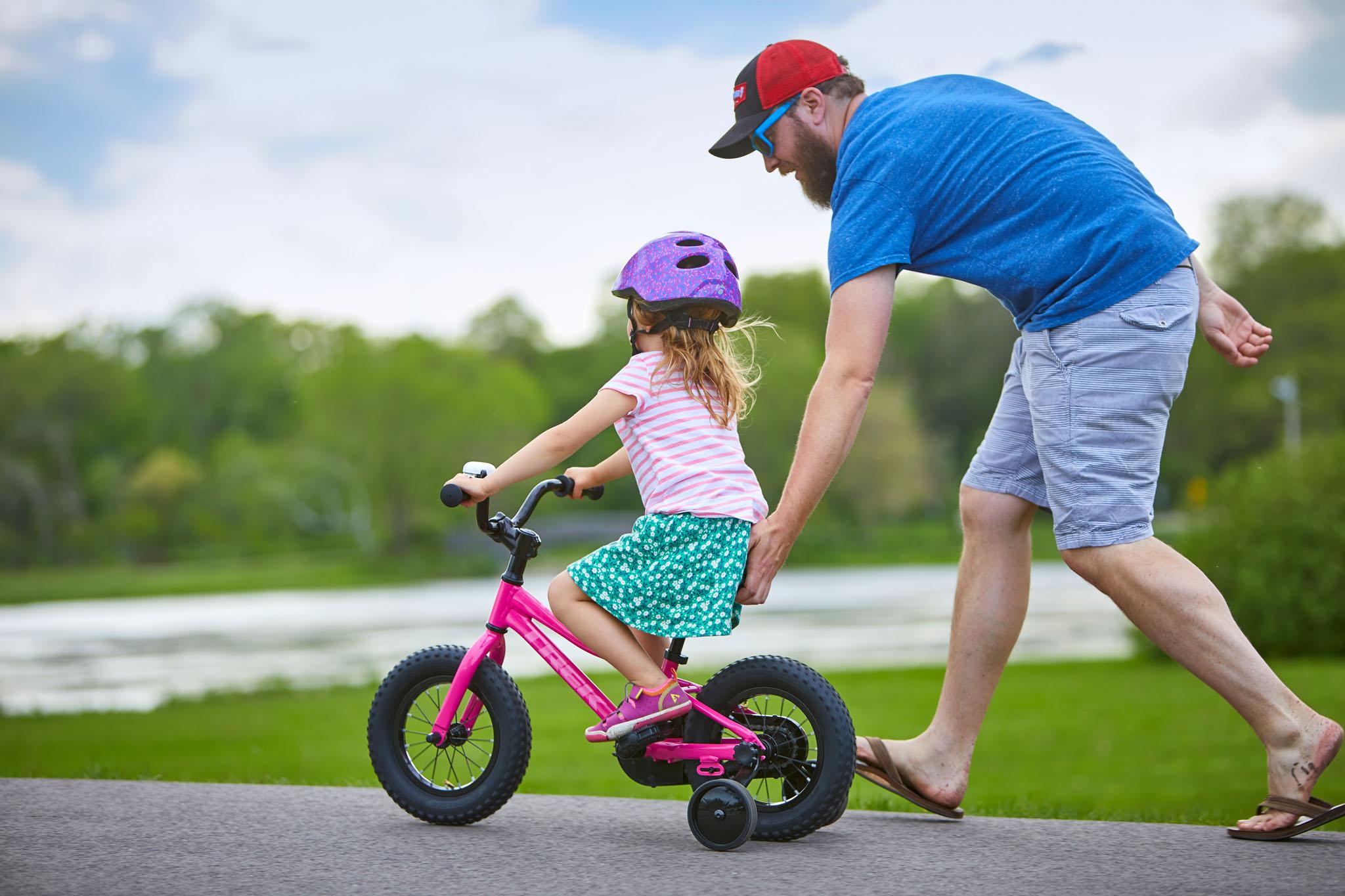 Tēvs stumj meitu uz viņas jaunā Trek Precaliber velosipēda